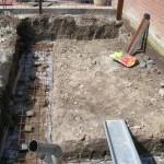 Ontgraven van funderingsleuf incl. de wapening en het storten van beton.