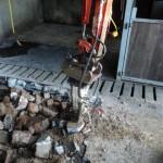 Sloopwerk betonnen vloer door middel van sloophamer aan mini graver